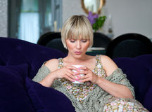 Woman with coffee on sofa Royalty Free Stock Photos