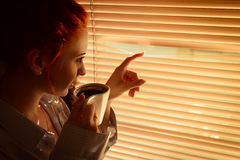 Woman with coffee stares through blinds early morning Royalty Free Stock Images