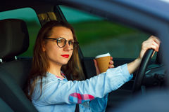 Woman with coffee to go driving her car Royalty Free Stock Photo