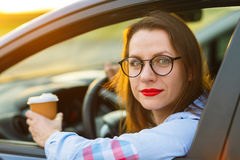 Woman with coffee to go driving her car Royalty Free Stock Image
