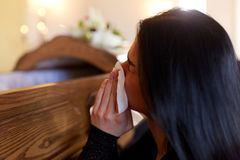 Woman with coffin crying at funeral in church Stock Image