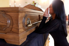 Woman with coffin crying at funeral in church. People and mourning concept - crying woman with coffin at funeral in church royalty free stock photo