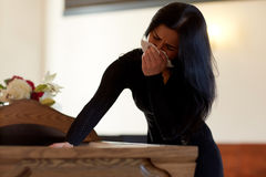 Woman with coffin crying at funeral in church. People and mourning concept - crying woman with coffin at funeral in church royalty free stock photography