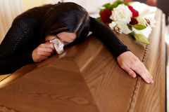 Woman with coffin crying at funeral in church Royalty Free Stock Images