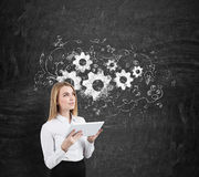 Woman and cogs and gears on a blackboard Royalty Free Stock Photography