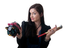 Woman coinbank hammer. A young woman holding a piggy bank and a hammer looking unsure Stock Photo