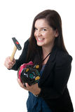 Woman coinbank hammer smile. A young adult woman holding a pig bank and a hammer smiling Stock Image