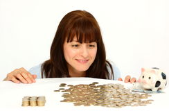 Woman and coins. Smiling woman looking at stack of coins (money) isolated on a white background Royalty Free Stock Photography
