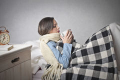 Woman with a cold. Woman into bed drinking something hot for the cold Stock Photography