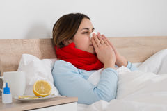 Woman With Cold Blowing Her Nose Royalty Free Stock Photos