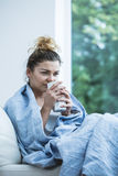 Woman with cold drinking tea Royalty Free Stock Photo