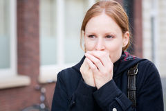 Woman with Cold Hands in the Fall. Closeup portrait of a young woman warming up her hands with her breath. Photographed in the autumn on a city street Royalty Free Stock Photography
