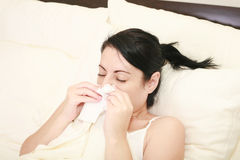 Woman with cold sneezing Stock Images