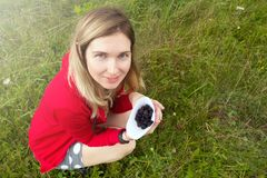 Woman collecting blackberry in the meadow. Happy woman and wild royalty free stock photos