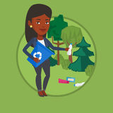 Woman collecting garbage in forest. Stock Photo