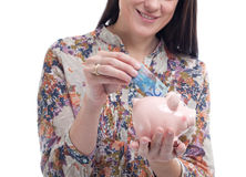 Woman collecting money in a piggy bank Royalty Free Stock Photography