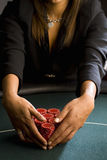 Woman collecting piles of gambling chips on table, mid section Royalty Free Stock Images