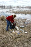 Woman collecting rubbish in nature. Woman collecting rubbish (trash) on a lake shore during an environmental clean-up program Royalty Free Stock Image