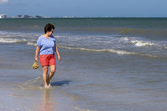 Woman collecting shells in the surf in the Gulf of Mexico Stock Photography