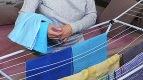 Woman collects blue dry towels stock footage