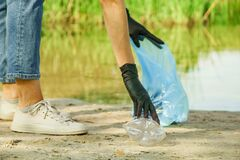Woman collects garbage plastic trash bottle in bag rubbish