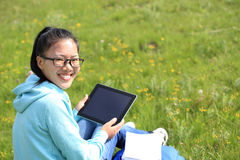 Woman college student use tablet pc sit on grass Stock Photography