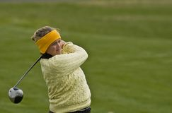 Woman collegiate golfer swinging driver stock image