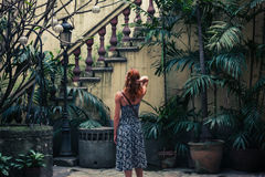 Woman by colonial staircase. A young woman is admiring an old colonial staircase in a courtyard Stock Photos