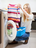 Woman with color clothes near washing machine Royalty Free Stock Image