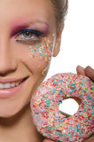 Woman with color decorations on face and donut Stock Photos