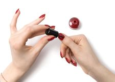 Woman color her red nails. On white with shadows royalty free stock photos