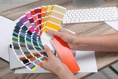 Woman with color palette samples at table. Closeup stock photography