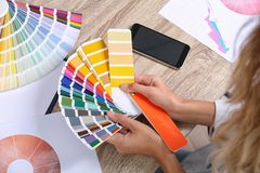 Woman with color palette samples at table. Closeup stock image