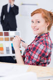 Woman with the color picker and pencil in her hand. Woman sitting close to the drafting board with the color picker and pencil in her hand and a men in suit Royalty Free Stock Image