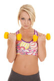 Woman color sports bra two weights up Royalty Free Stock Photos