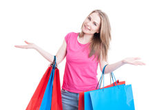 Woman with colored shopping bags acting cheerful and smiling Royalty Free Stock Photos