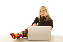 Woman colored socks sit by computer shocked Stock Photos