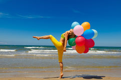 Woman with colorful balloons on the beach Royalty Free Stock Photography