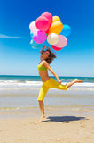 Woman with colorful balloons on the beach Stock Image