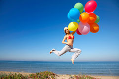 Woman with colorful balloons jumping Royalty Free Stock Photos