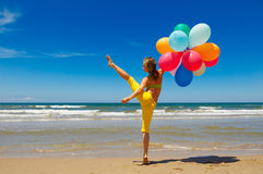 Woman with colorful balloons jumping on the beach Stock Images