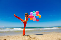 Woman with colorful balloons jumping on the beach Royalty Free Stock Photos