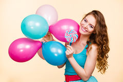 Woman with colorful balloons and lollipop. Woman attractive cheerful girl holding colorful balloons and sweet lollipop in hands. Summer holidays, celebration and Stock Image