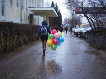 Woman with colorful balloons. Walking on the street Royalty Free Stock Image