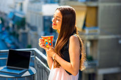 Woman with colorful coffee cup on the balcony. Young woman enjoying coffee in bright and colorful cup on the balcony in the city Royalty Free Stock Photography