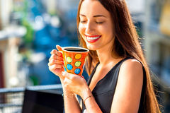 Woman with colorful coffee cup on the balcony. Young woman enjoying coffee in bright and colorful cup on the balcony in the city Stock Photography