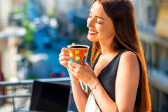Woman with colorful coffee cup on the balcony Stock Photography