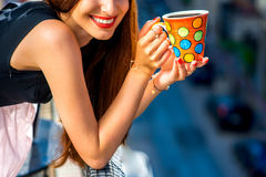 Woman with colorful coffee cup on the balcony Royalty Free Stock Photo