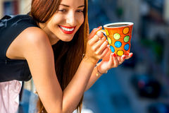 Woman with colorful coffee cup on the balcony Royalty Free Stock Photos