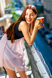 Woman with colorful coffee cup on the balcony Stock Images